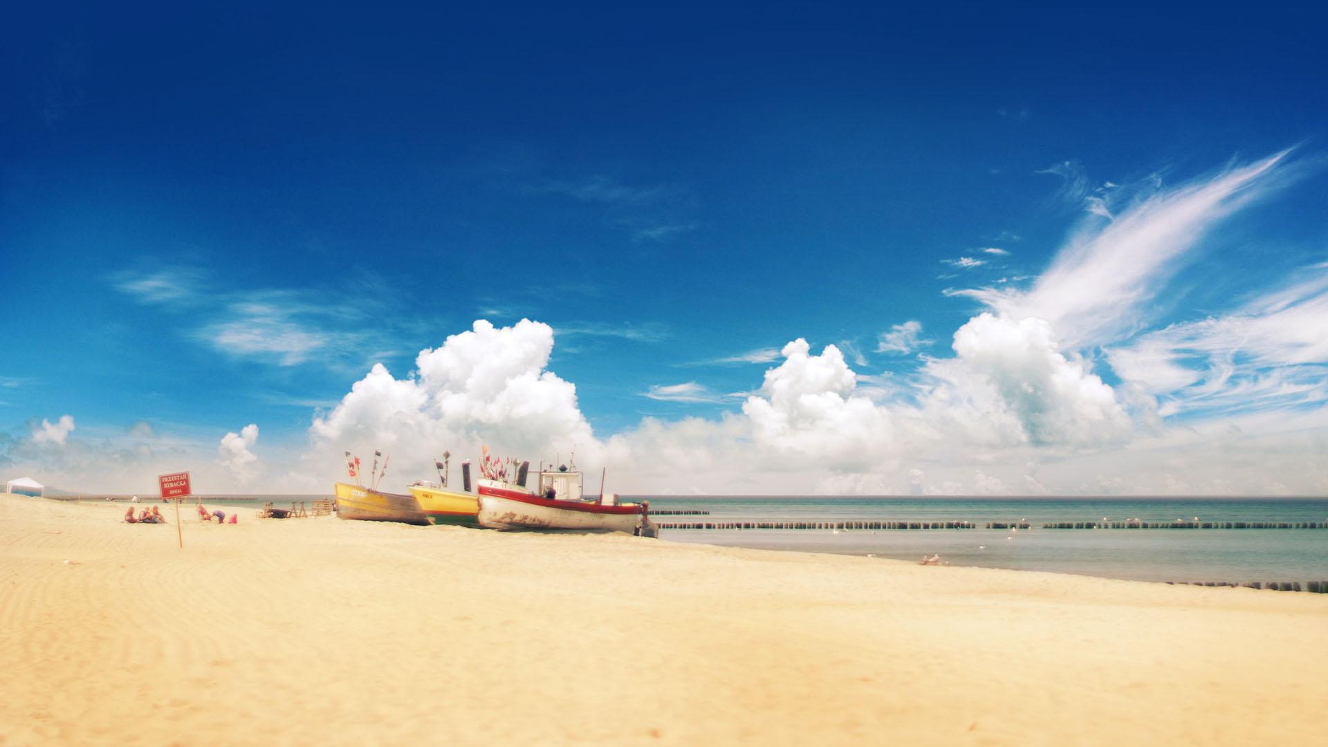 Rewalska piaszczysta plaża w pogodny dzień. Na tle spokojnego Bałtyku przystań rybacka.